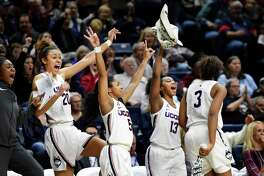 Connecticut's Olivia Nelson-Ododa (20), Crystal Dangerfield (5), Christyn Williams (13) and Megan Walker (3) cheer for a teammate during the second half of an NCAA college basketball game against Tulsa, Sunday, Jan. 19, 2020, in Storrs, Conn. (AP Photo/Stephen Dunn)
