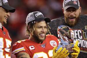 Kansas City Chiefs' Tyrann Mathieu is flanked by Patrick Mahomes, left, and Travis Kelce as he holds the Lamar Hunt Trophy after the NFL AFC Championship football game against the Tennessee Titans Sunday, Jan. 19, 2020, in Kansas City, MO. The Chiefs won 35-24 to advance to Super Bowl 54. (AP Photo/Charlie Riedel)