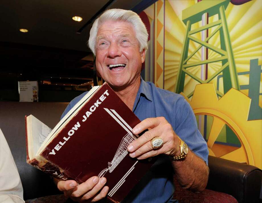 Former Super Bowl-winning coach with the Dallas Cowboys and Port Arthur native Jimmy Johnson, holds his 1961 senior yearbook,  Yellow Jacket, before singing it for a former classmate after his arrival at the Port Arthur Holiday Inn for his 50th class reunion. Johnson is a 1961 graduate from Thomas Jefferson High School in Port Arthur.   Friday,  June 24, 2011.  Valentino Mauricio/The Enterprise Photo: Valentino Mauricio