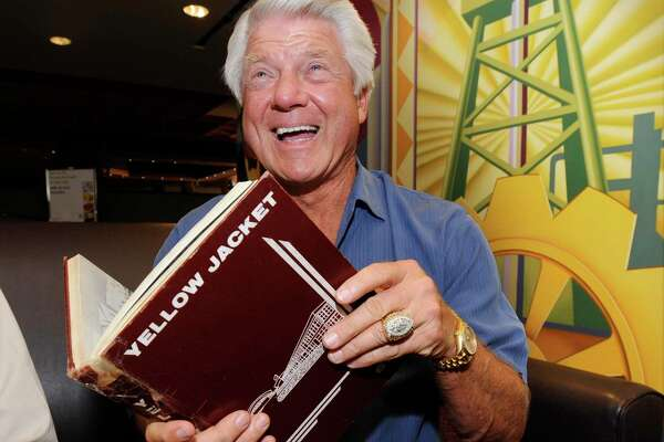 Former Super Bowl-winning coach with the Dallas Cowboys and Port Arthur native Jimmy Johnson, holds his 1961 senior yearbook, Yellow Jacket, before singing it for a former classmate after his arrival at the Port Arthur Holiday Inn for his 50th class reunion. Johnson is a 1961 graduate from Thomas Jefferson High School in Port Arthur. Friday, June 24, 2011. Valentino Mauricio/The Enterprise