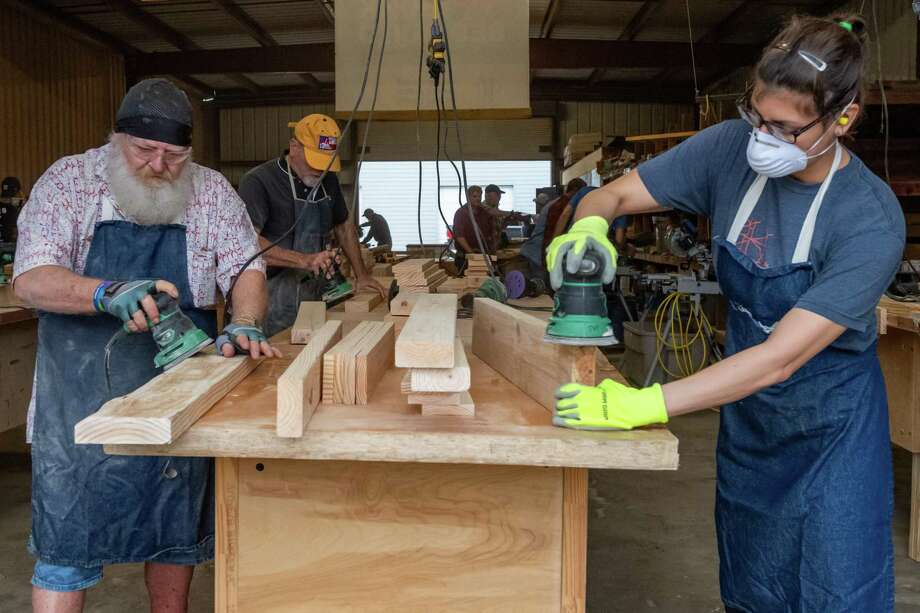 John Wright, left, and Megan Smith sand pieces used to construct headboards for a child's bed. The Beaumont chapter of Sleep In Heavenly Peace held a build day on Saturday, January 18, 2020 in their production facility on Milam Street where about 40 volunteers worked to build beds for kids that don't have any.