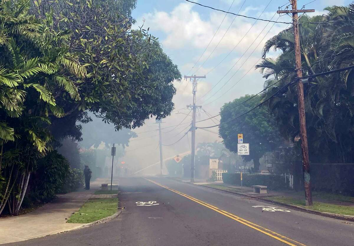 Smoke billows through the streets after a shooting in Honolulu, Sunday, Jan. 19, 2020. The Honolulu Star-Advertiser reports that officers had responded to an assault call when they encountered a male with a firearm, who then opened fire, striking two officers. (AP Photo/Marco Garcia)