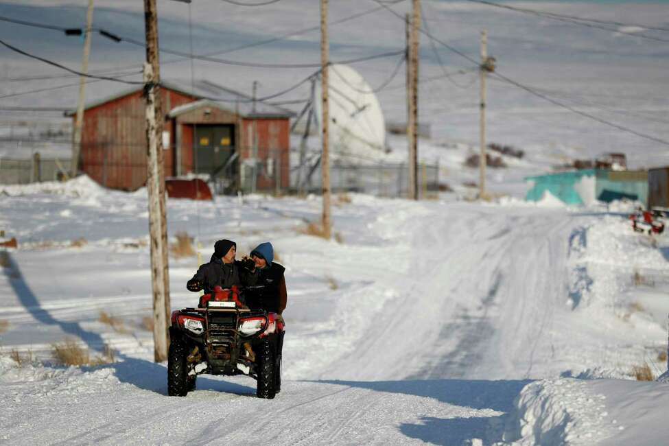 People ride through town on all-terrain vehicles Saturday, Jan. 18, 2020, in Toksook Bay, Alaska. The first Americans to be counted in the 2020 Census starting Tuesday, Jan. 21, live in this Bering Sea coastal village. The Census traditionally begins earlier in Alaska than the rest of the nation because frozen ground allows easier access for Census workers, and rural Alaska will scatter with the spring thaw to traditional hunting and fishing grounds. (AP Photo/Gregory Bull)