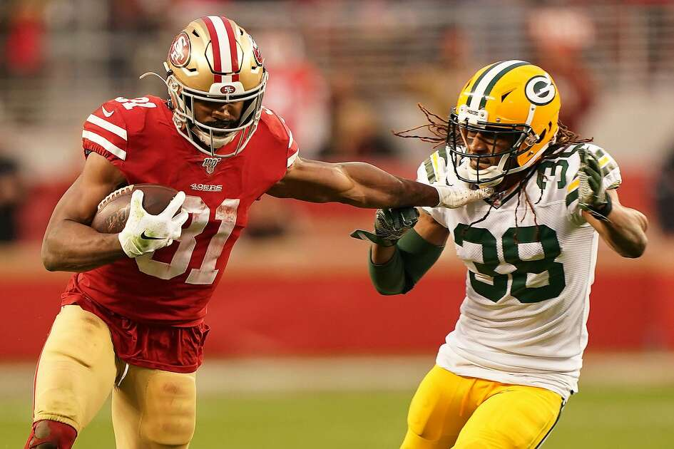 SANTA CLARA, CALIFORNIA - JANUARY 19: Raheem Mostert #31 of the San Francisco 49ers stiff arms Tramon Williams #38 of the Green Bay Packers on a run during the NFC Championship game at Levi's Stadium on January 19, 2020 in Santa Clara, California. (Photo by Thearon W. Henderson/Getty Images)
