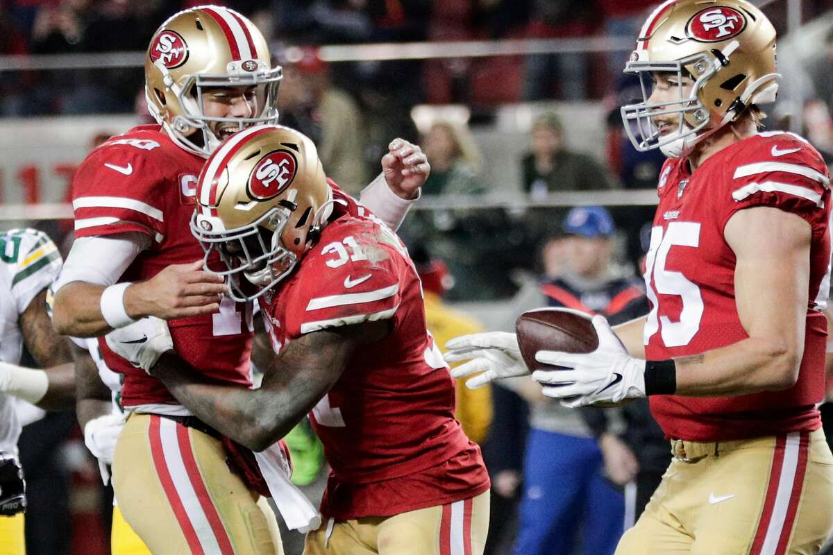 San Francisco 49ers' Jimmy Garoppolo and Raheem Mostert react to Mostert's touchdown in the third quarter during the NFC Championship game between the San Francisco 49ers and the Green Bay Packers at Levi's Stadium on Sunday, Jan. 19, 2020 in Santa Clara, Calif.