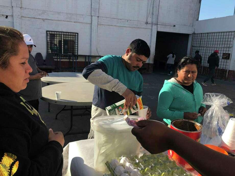 En esta foto del 11 de enero de 2020, Joel Cáceres, centro, vierte leche en su café mientras otros solicitantes de asilo compran comida en un refugio para migrantes de Mexicali, México. Photo: Elliot Spagat /Associated Press / Copyright 2020 The Associated Press. All rights reserved.