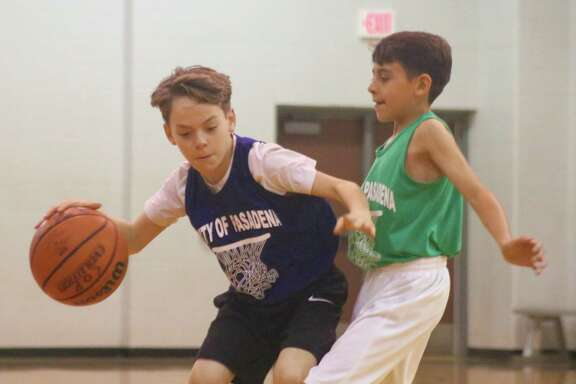 The South Belt Underdog's Hunter Ford attempts to dribble around the defense of a Rockets player during their Saturday afternoon season opener.