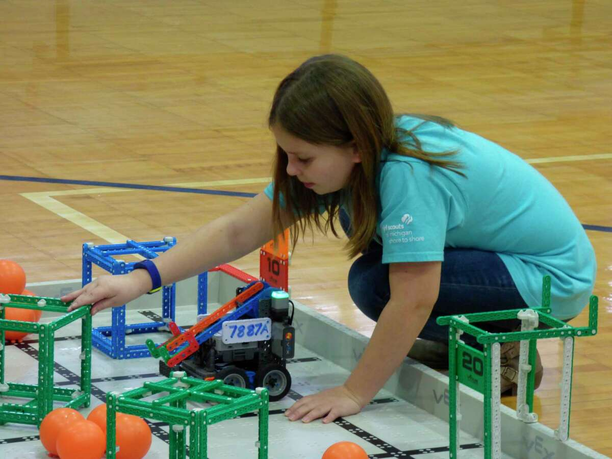 Competitors at the VEX IQ challenge at Manistee Catholic Central on Saturday test their programming and piloting skills through a series of games. This student prepares her robot for an autonomous run, which utilizes programming rather than a remote control to guide the machine. (Scott Fraley/News Advocate)