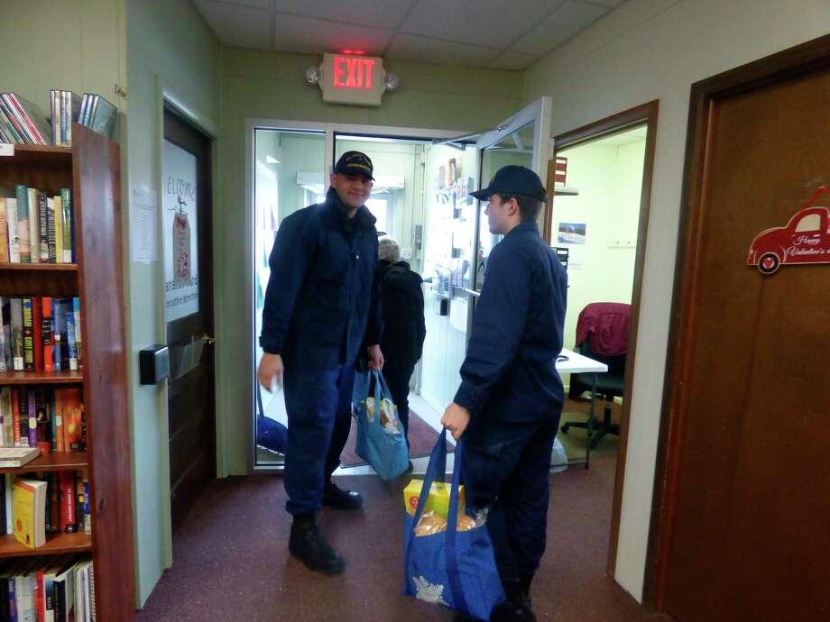 Coast guard servicemen, Tafatafa Sataua (left) andDevon Larson (right) carry groceries for elderly residentsduring the senior food bank held Friday, Jan. 17.(Scott Fraley/News Advocate)