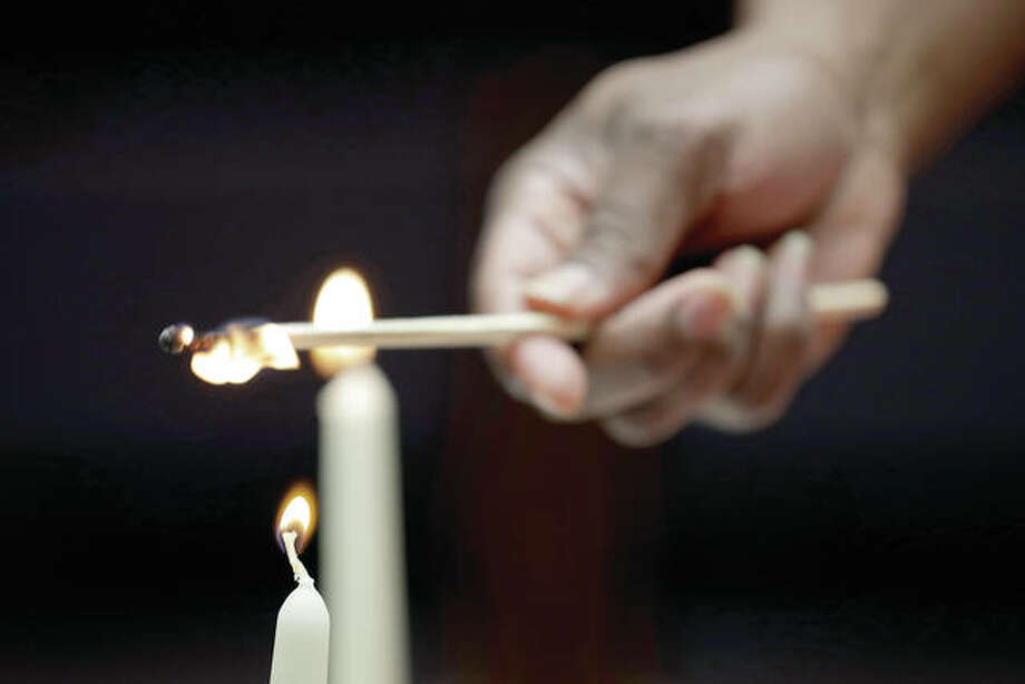 Corey Caver lights candles before a Shabbat Service at KAM Isaiah Israel in Chicago.