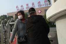 A woman (L) leaves the Wuhan Medical Treatment Centre, where a man who died from a respiratory illness was confined, in the city of Wuhan, Hubei province, on January 12, 2020. - A 61-year-old man has become the first person to die in China from a respiratory illness believed caused by a new virus from the same family as SARS, which claimed hundreds of lives more than a decade ago, authorities said. (Photo by Noel Celis / AFP) (Photo by NOEL CELIS/AFP via Getty Images)