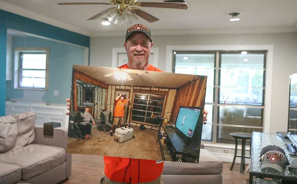 Astros fan Jim Dean holds a photo of him watching Game 6 of the World Series that went viral from his home in Pearland after it was gutted during Hurricane Harvey.