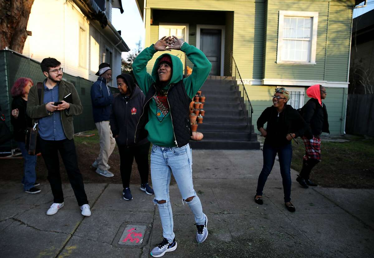 """Moms 4 Housing member Misty Cross dances to the hip-hop song, """"If I Ruled the World,"""" outside the house she and other homeless mothers occupied in Oakland, Calif., on Tuesday, January 14, 2020. Cross along with fellow Moms 4 Housing member Tolani King were arrested during an eviction early on Tuesday morning."""