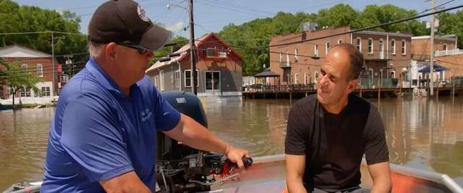 "Grafton Mayor Rick Eberlin, left, shows his flooded village to Marcus Lemonis of ""The Profit"" in June. At 9 p.m. Tuesday, the CNBC program will focus on Grafton's flood battles this year."