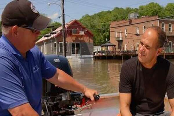 """Grafton Mayor Rick Eberlin, left, shows his flooded village to Marcus Lemonis of """"The Profit"""" in June. At 9 p.m. Tuesday, the CNBC program will focus on Grafton's flood battles this year."""