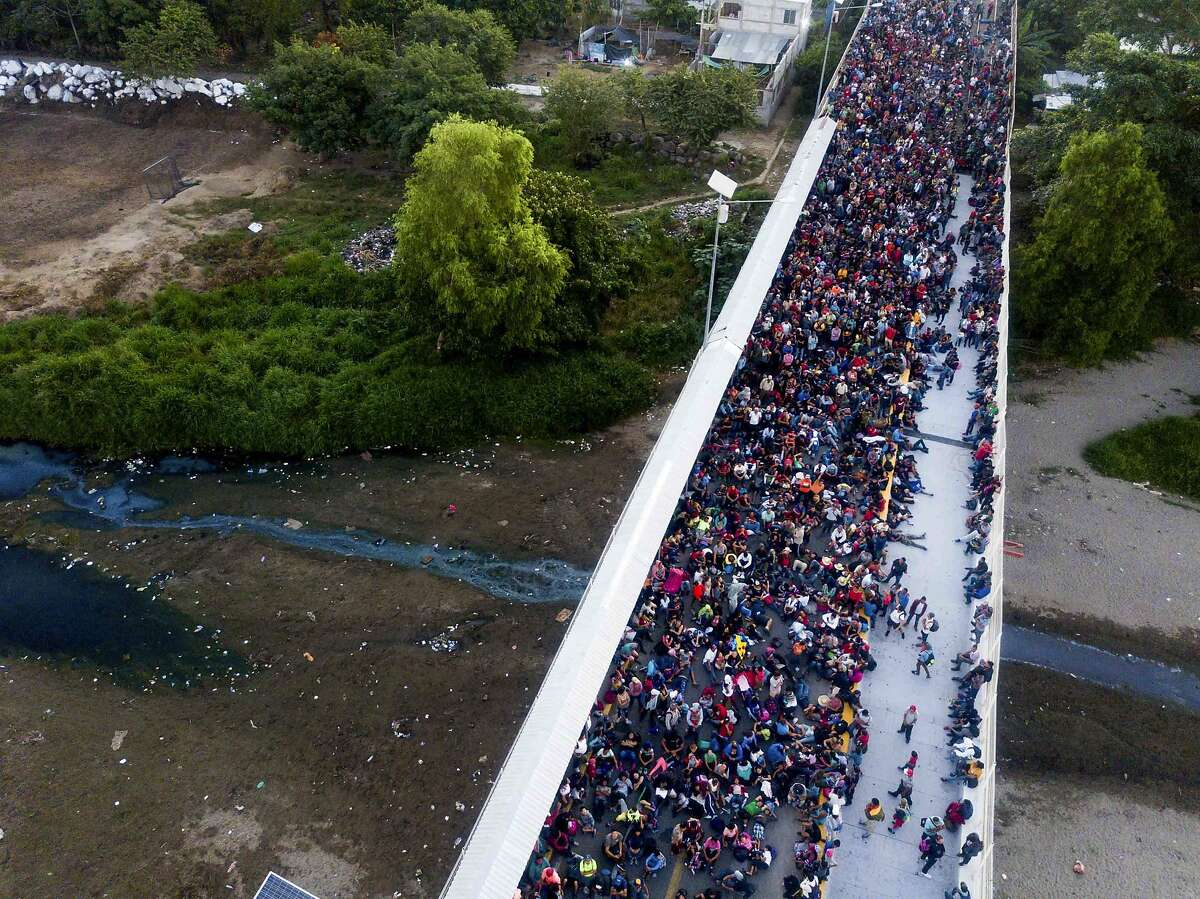 Migrants gather at the bridge spanning the Suchiate River in Tecun Uman, Guatemala, Monday, Jan. 20, 2020. More than a thousand Central American migrants hoping to reach United States marooned in Guatemala were preparing to walk en masse across a bridge leading to Mexico in an attempt to convince authorities there to allow them passage through the country. (AP Photo/Santiago Billy)
