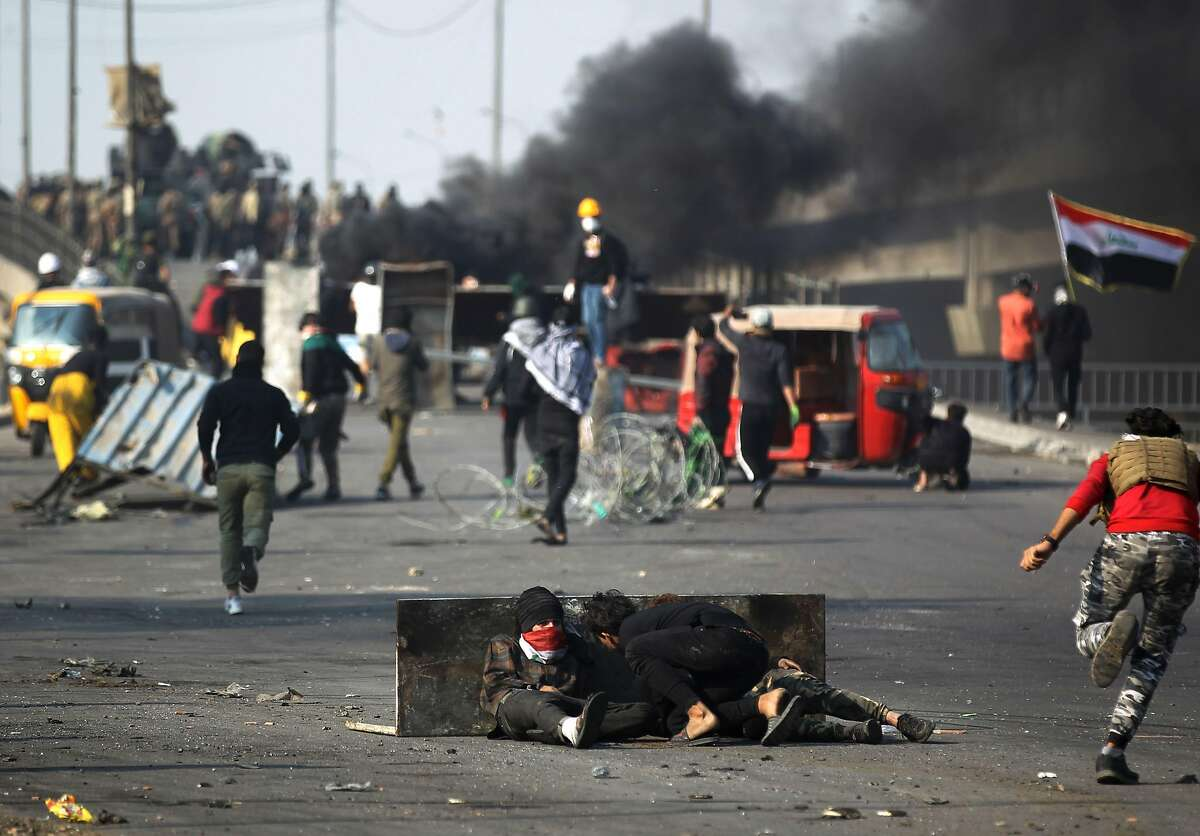 Iraqi protesters take cover amid clashes with riot police following a demonstration at Baghdad's Tayaran Square, east of Tahrir Square, on January 20, 2020. - Three Iraqi protesters were killed in the capital as thousands of anti-government demonstrators sought to shut streets across the country today, their deadline for authorities to implement long-awaited reforms. (Photo by AHMAD AL-RUBAYE / AFP) (Photo by AHMAD AL-RUBAYE/AFP via Getty Images)