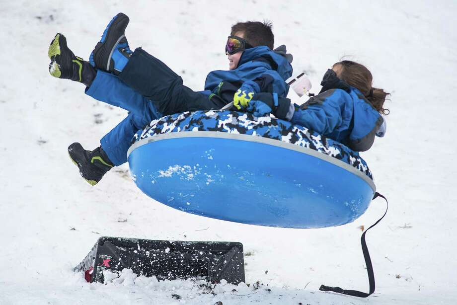 Ashley McCain and brother, Alex, take a jump on a sled at the G&B Community Culture Center in Wilton on Sunday, Jan. 19. A snow storm over the weekend helped Wiltonians looking for a little winter fun. Photo: Bryan Haeffele / Hearst Connecticut Media / Hearst Connecticut Media