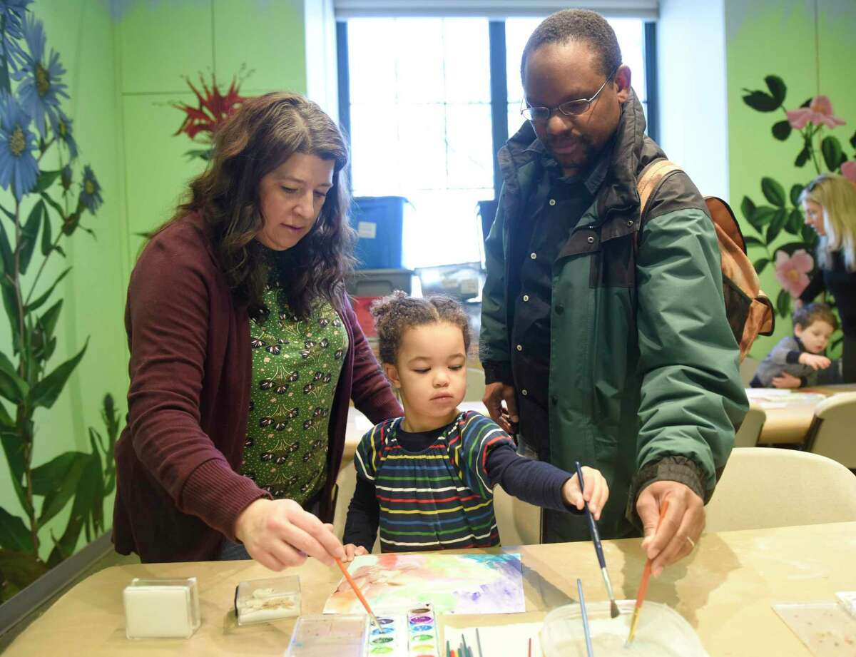 """Ally Cole, 3, of Scarsdale, N.Y., paints watercolors with her parents Jeanine Cole and Brandon Cole during Martin Luther King Jr. Family Day at the Bruce Museum in Greenwich, Conn. Monday, Jan. 20, 2020. The event featured a performance of """"A So-Long Journey: The Early Years of Phillis Wheatley"""" by Karima A. Robinson, Ph.D. Wheatley was the first published female African American poet and a key figure in the early Abolitionist movement."""