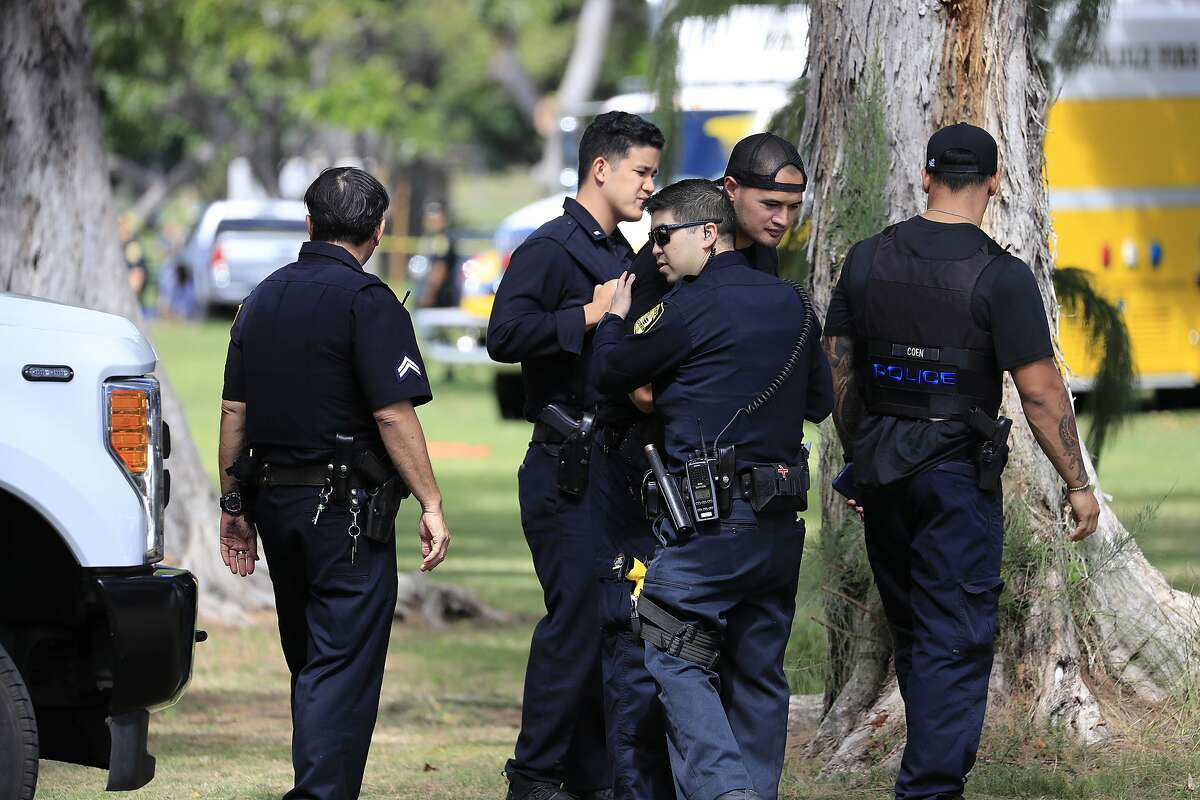 Honolulu police officers gather near the scene of a shooting near Diamond Head State Monument on Sunday, Jan. 19, 2020, in Honolulu. (AP Photo/Marco Garcia)