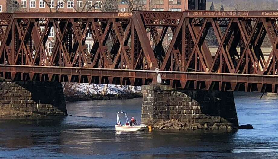 Firefighters rescued a person who fell in the Housatonic River from a railroad bridge last night. The personm who managed to swim to the base of a pillar for the railroad bridge, stayed there until they were rescued. Photo: Storm Engine Co. /Ambulance Corps