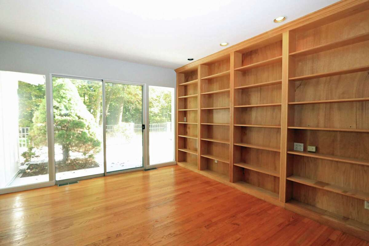 The study has floor-to-ceiling bookshelves and sliding doors to the large wood deck and backyard.