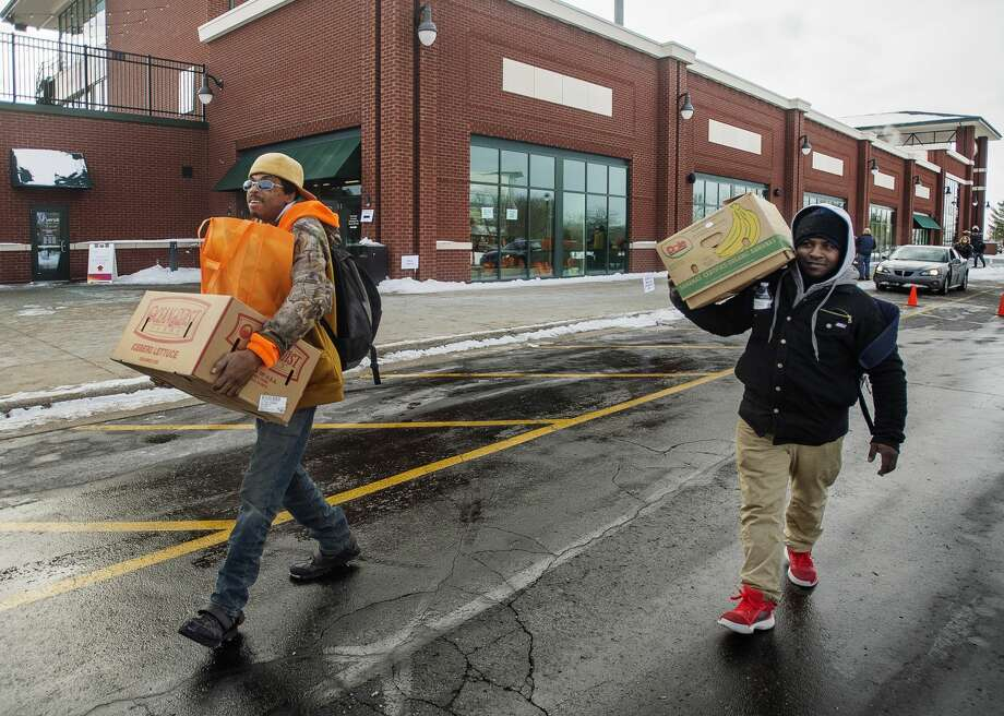 """Justin """"Beetlejuice"""" Grimm, left, and Quan Porter, right, carry boxes of food items to a vehicle after receiving them during a food distribution event hosted by The Arc of Midland, Hidden Harvest and Food Bank of Eastern Michigan in celebration of Martin Luther King Jr. Day Monday, Jan. 20, 2020 at Dow Diamond. (Katy Kildee/kkildee@mdn.net) Photo: (Katy Kildee/kkildee@mdn.net)"""