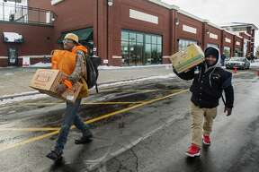 """Justin """"Beetlejuice"""" Grimm, left, and Quan Porter, right, carry boxes of food items to a vehicle after receiving them during a food distribution event hosted by The Arc of Midland, Hidden Harvest and Food Bank of Eastern Michigan in celebration of Martin Luther King Jr. Day Monday, Jan. 20, 2020 at Dow Diamond. (Katy Kildee/kkildee@mdn.net)"""