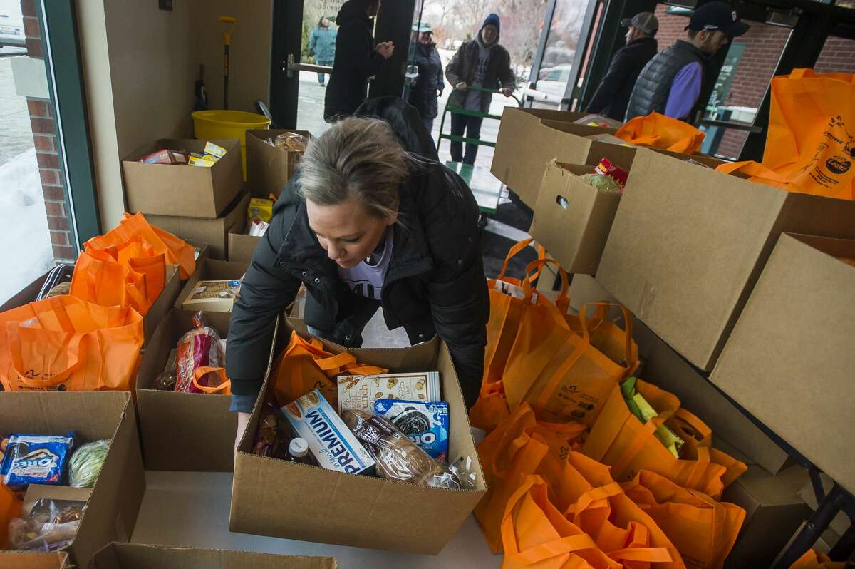 Volunteers transport boxes of food items during a food distribution event hosted by The Arc of Midland, Hidden Harvest and Food Bank of Eastern Michigan in celebration of Martin Luther King Jr. Day Monday, Jan. 20, 2020 at Dow Diamond. (Katy Kildee/kkildee@mdn.net)