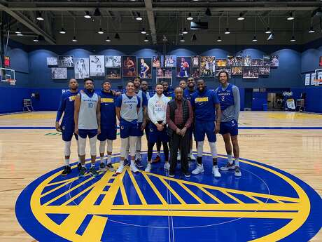 Clarence B. Jones — the former personal counsel, advisor and speech writer for Martin Luther King Jr. — poses with the Warriors after visiting practice last month.