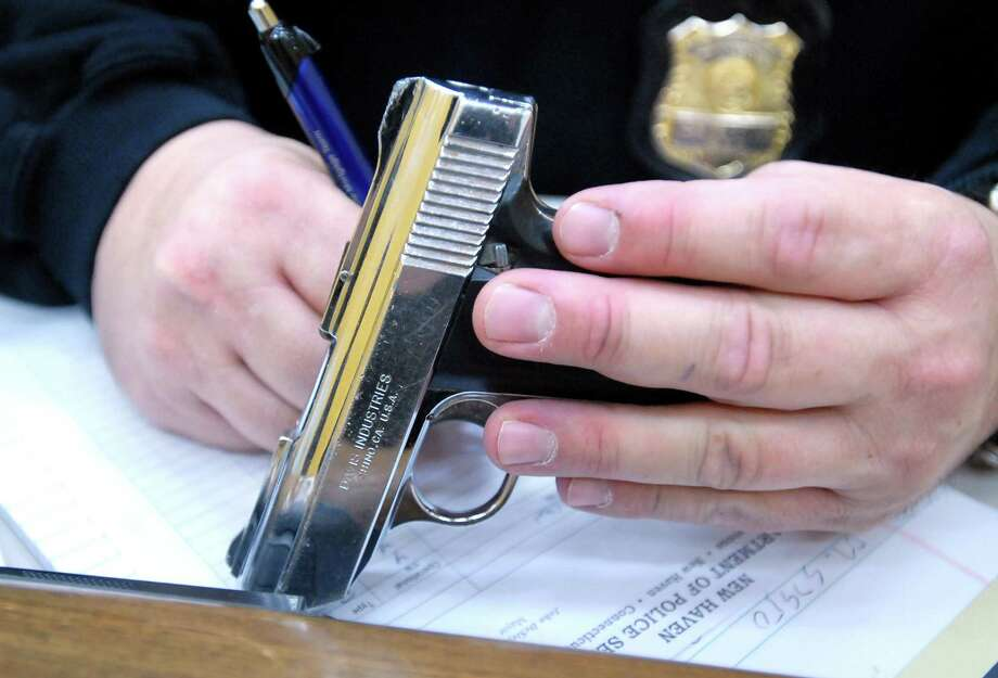 A New Haven Police detective writes down the serial number of a handgun brought into the New Haven Police Department during a gun buyback program in 2007. Photo: File Photo