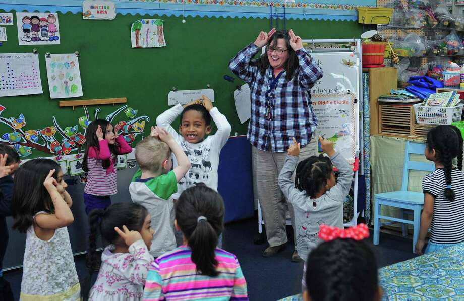 Side by Side Charter School Pre-Kindergarten teacher Judy Arroyo-Goldstein sings an interactive song with her class Friday, April 7, 2017, at the school in Norwalk, Conn. The School is celebrating its 20th anniversary and has announced construction plans for a new school building to house their middle school students. Photo: Erik Trautmann / Hearst Connecticut Media / Norwalk Hour