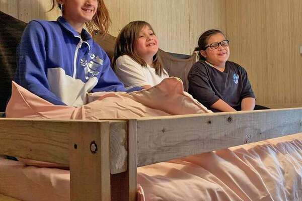 Three kids smile as they receive their beds from Sleep in Heavenly Peace.