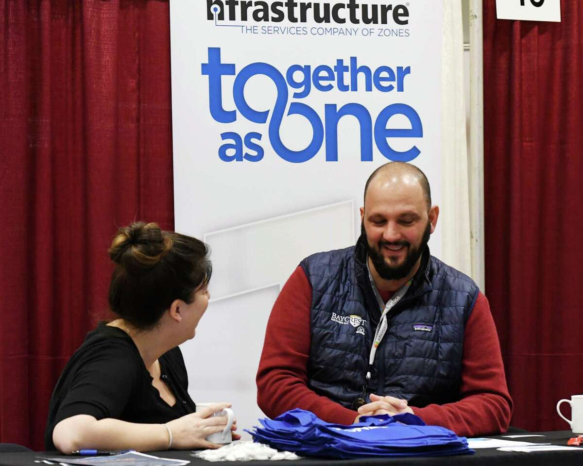 Meaghan Johnson, left, and Dan Riccio, right, with Zones, staff their recruitment booth during the Times Union Job Fair on Monday, Jan. 20, 2020, at the Albany Marriott Hotel in Colonie, N.Y. (Will Waldron/Times Union)