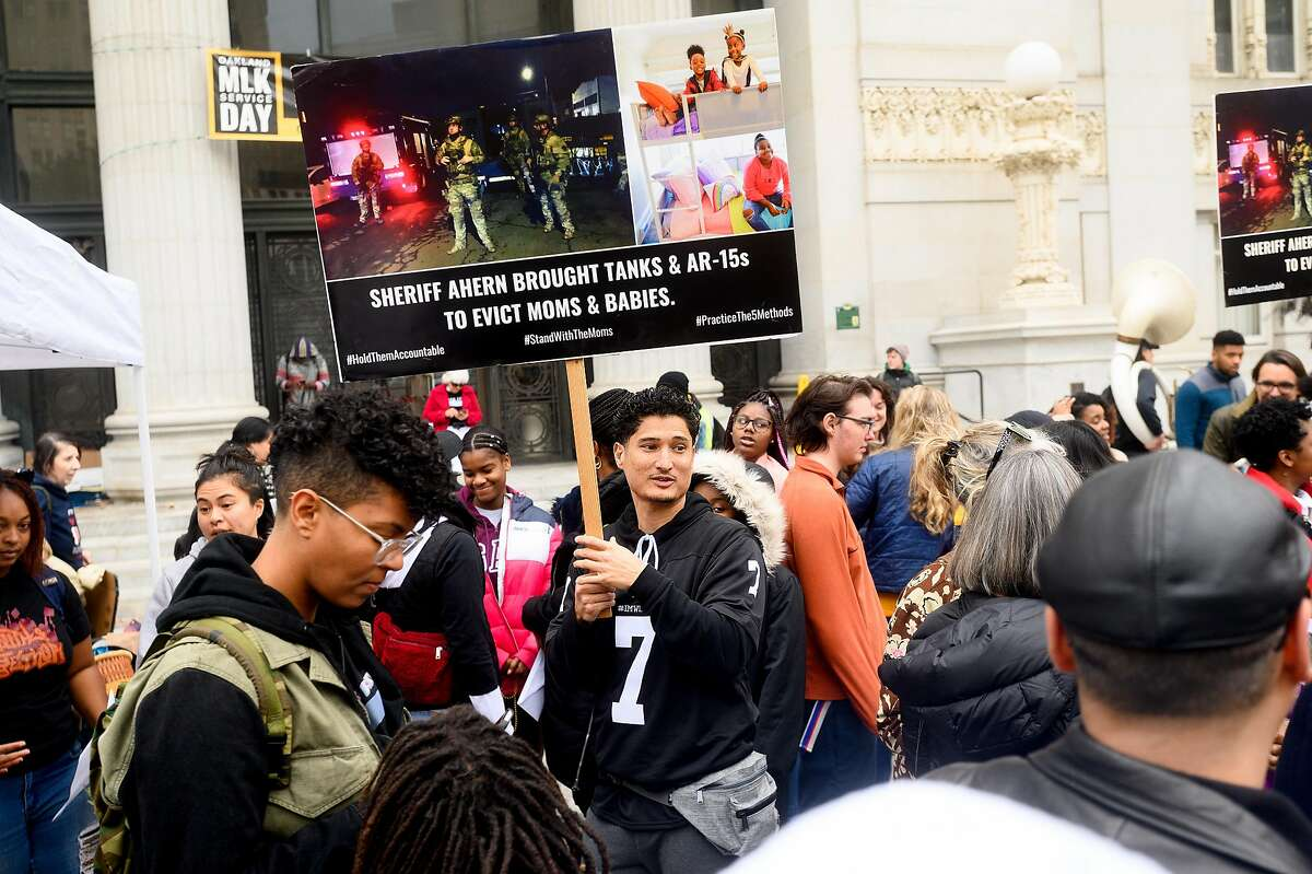 Sinukuan Laban holds a sign denouncing police actions against Moms 4 Housing during a rally against police violence on Monday, Jan. 20, 2020, in Oakland, Calif.