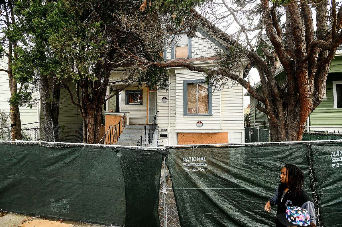 Pedestrians pass 2928 Magnolia St. on Monday, Jan. 20, 2020, in Oakland, Calif. Previously occupied by Moms 4 Housing activists, the home may be sold to the Oakland Community Land Trust, a nonprofit organization that facilitates affordable housing, according to the Oakland Mayor's office.