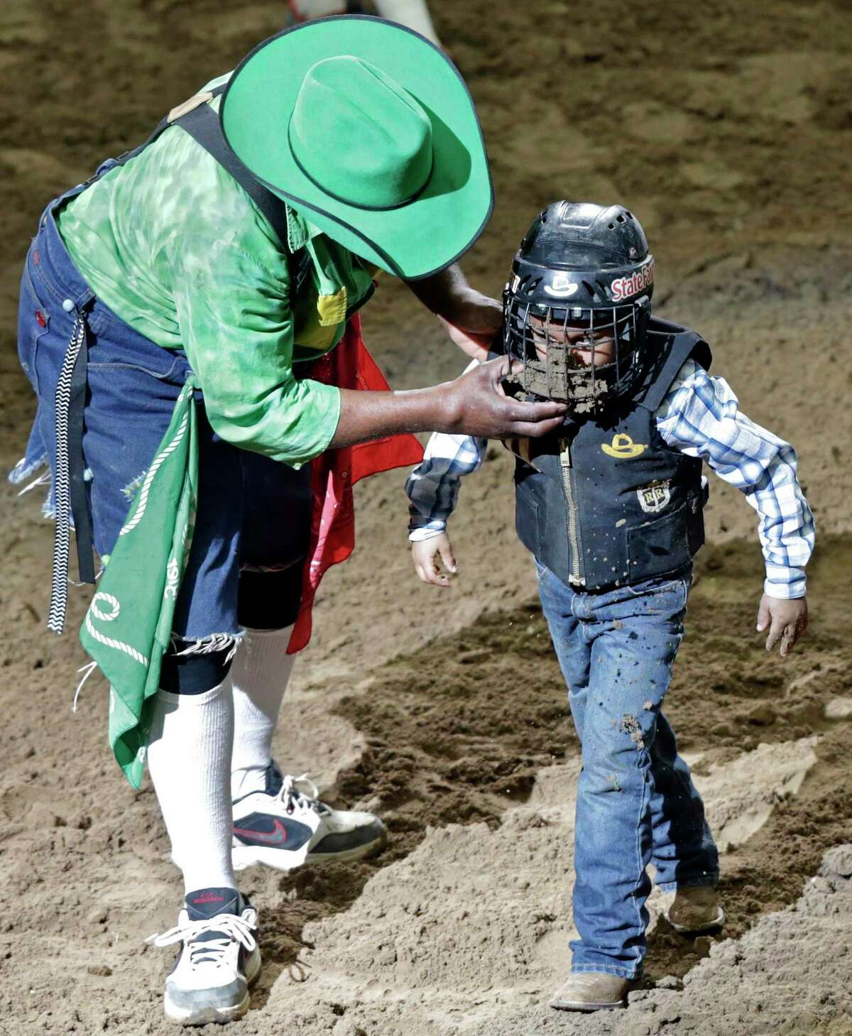 Rodeo clown Leon Coffee helps to remove mud out of a rider's face mask at the 2019 rodeo. A mouthful of dirt is sometimes a riders' only reward.