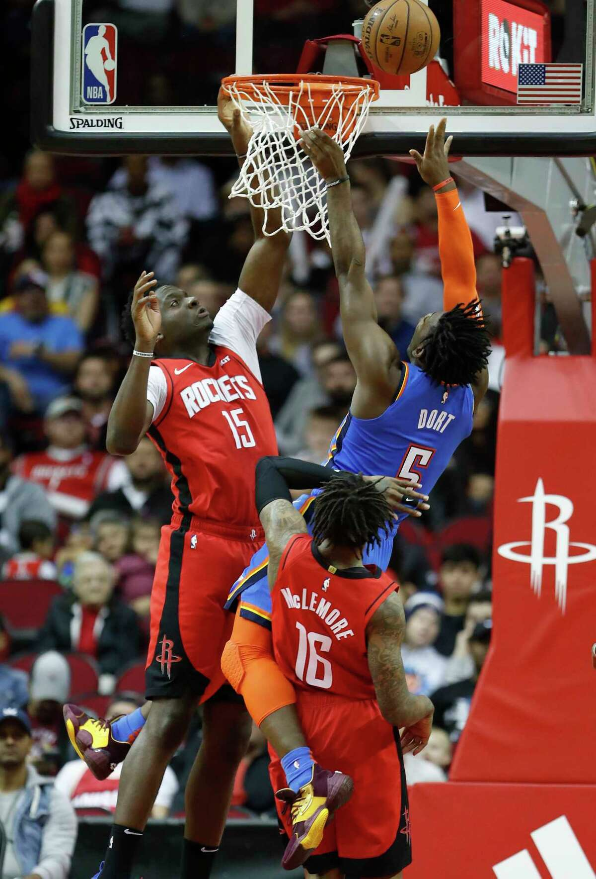 Oklahoma City Thunder guard Luguentz Dort (5) and Houston Rockets center Clint Capela (15) and guard Ben McLemore (16) under the basket during the first half of an MBA basketball game at Toyota Center, in Houston, Monday, Jan. 20, 2020.