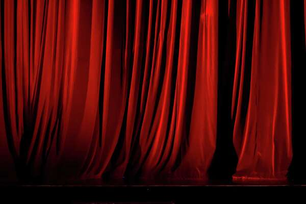 A community theater has suspended indefinitely a director accused in a lawsuit of sexually assaulting three teenagers.