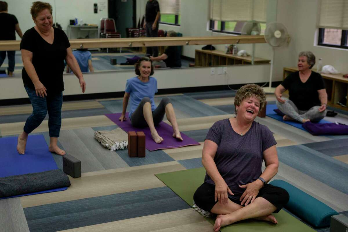 Randa Bruce-Gonzales can't help but laugh with classmates before the start of their yoga class at the San Antonio Oasis center, 700 Babcock Road, on Jan. 15. The center is for those who are 50 and older.