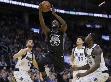 Golden State Warriors' Draymond Green (23) shoots between Dallas Mavericks' Maxi Kleber, left, Justin Jackson (44) and Dorian Finney-Smith, right, during the second half of an NBA basketball game Tuesday, Jan. 14, 2020, in San Francisco. (AP Photo/Ben Margot)