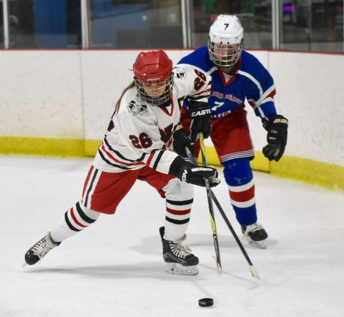 New Canaan's Sophie Potter (26) gets to the puck in front of West Haven/SHA's Jenna Hunt (7) on Monday.