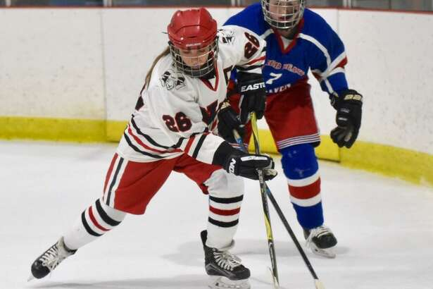 New Canaan's Sophie Potter (26) gets to the puck in front of West Haven/SHA's Jenna Hunt (7) during a girls ice hockey game at the Darien Ice House on Monday, Jan. 20, 2020.