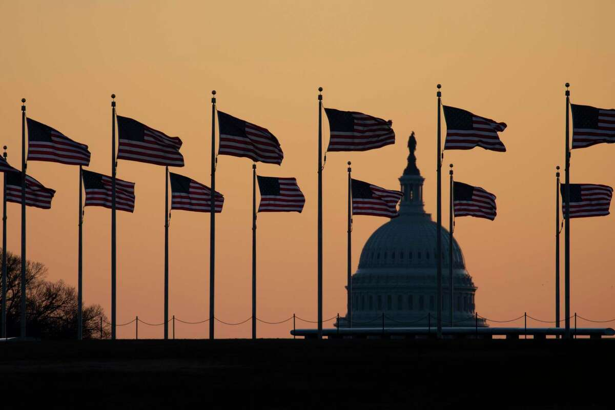 American flags blow in wind around the Washington Monument with the U.S. Capitol in the background at sunrise on Monday, Jan. 20, 2020, in Washington. The impeachment trial of President Donald Trump will resume in the U.S. Senate on Jan. 21. (AP Photo/Jon Elswick)