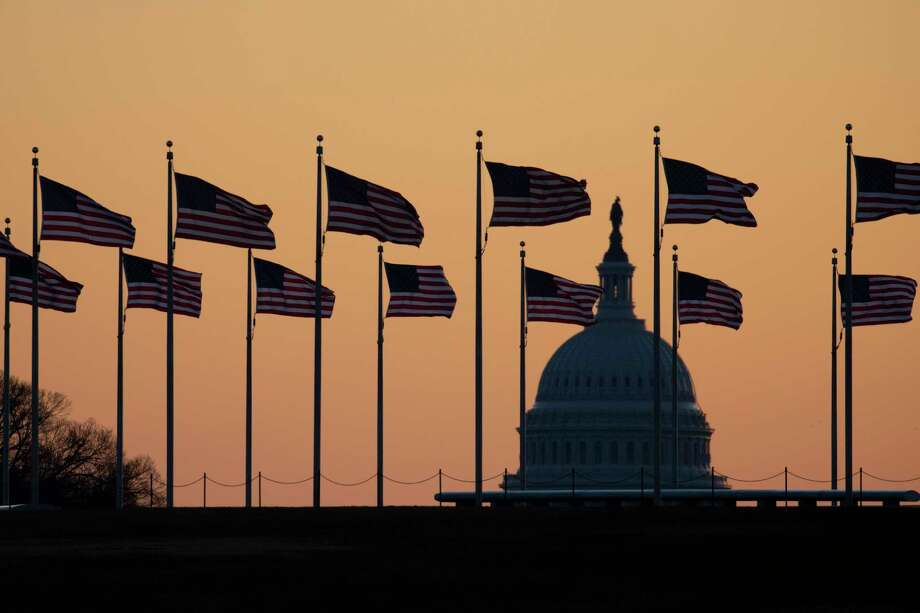 American flags blow in wind around the Washington Monument with the U.S. Capitol in the background at sunrise on Monday, Jan. 20, 2020, in Washington. The impeachment trial of President Donald Trump will resume in the U.S. Senate on Jan. 21.  (AP Photo/Jon Elswick) Photo: Jon Elswick / Copyright 2020 The Associated Press. All rights reserved.