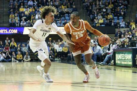 Texas guard Jase Febres (13) looks for a lane to drive on West Virginia forward Derek Culver during the first half Monday.
