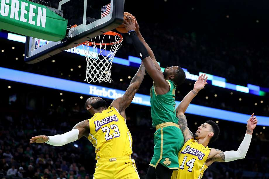 Jaylen Brown (middle) of the Celtics dunks over LeBron James (23) and Danny Green of the Lakers. Brown had 20 points. Photo: Maddie Meyer / Getty Images