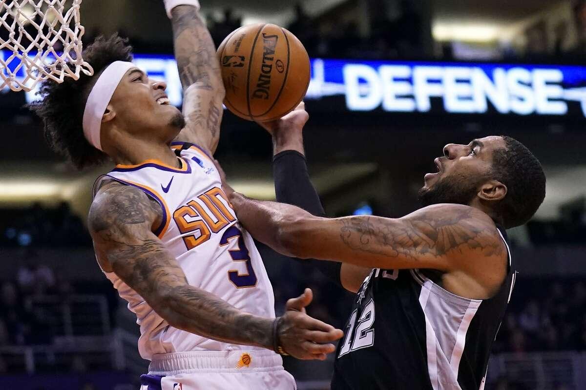 Phoenix Suns forward Kelly Oubre Jr. (3) blocks the shot of San Antonio Spurs center LaMarcus Aldridge (12) during the first half of an NBA basketball game, Monday, Jan. 20, 2020, in Phoenix. (AP Photo/Rick Scuteri)