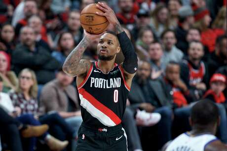 Portland Trail Blazers guard Damian Lillard shoots a 3-point basket against the Golden State Warriors during the second half of an NBA basketball game in Portland, Ore., Monday, Jan. 20, 2020. (AP Photo/Craig Mitchelldyer)