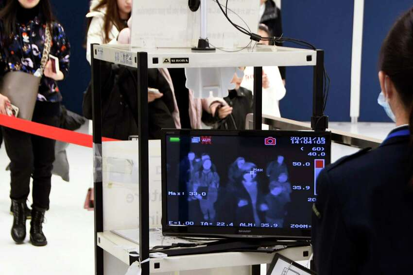 Jan. 16: Travelers from Wuhan in central China's Hubei province go through body temperature scanners at Narita airport near Tokyo, Japan. A fourth person died in the outbreak of the new coronavirus in China, authorities said, while Japan had confirmed a case of the virus on its shores.